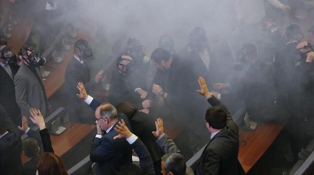 Parlamentos envueltos entre el humo causado por el lanzamiento del cartucho de gas lacrimógeno, en Pristina (Kosovo), este viernes.