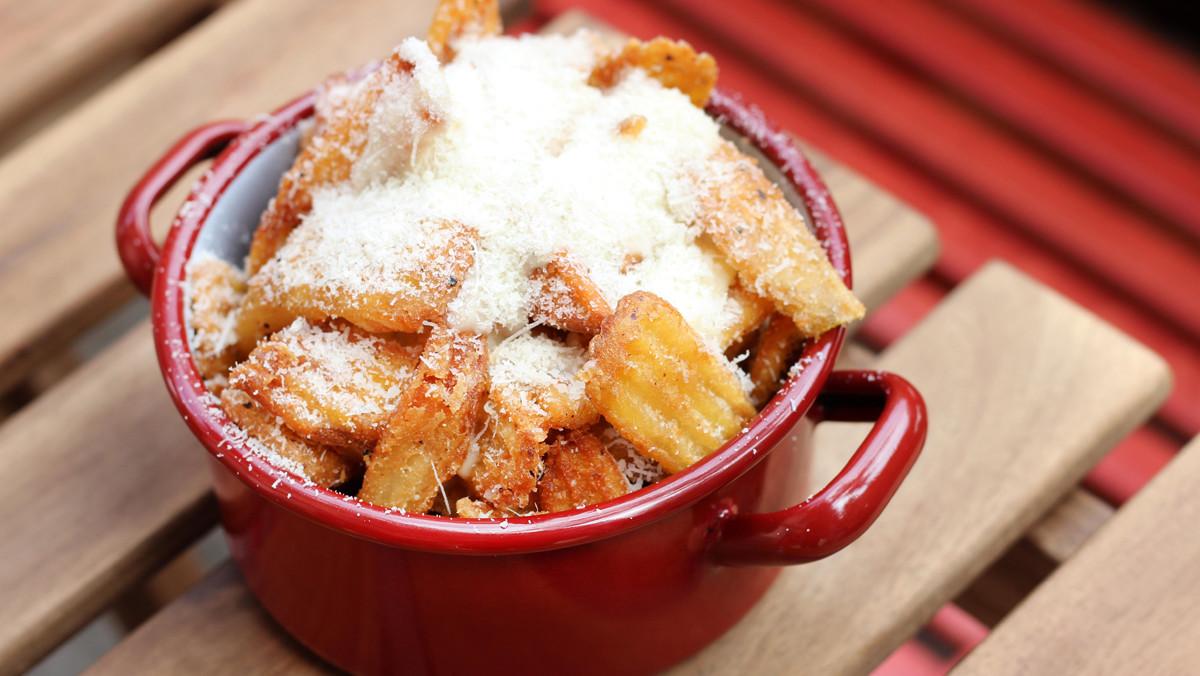 Patatas al aroma de trufa, con crema caliente de parmesano.