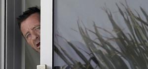 Phil Rudd, el batería de AC/DC, gesticula desde la ventana de su casa en Tauranga, Nueva Zelanda, este miércoles.