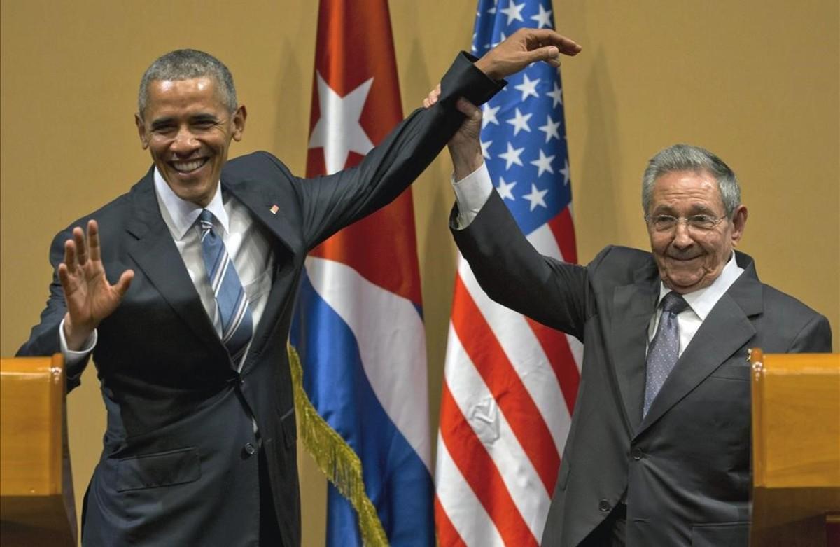 El presidente cubano, Raúl Castro, eleva el brazo del presidente Barack Obama en la conclusión de su conferencia de prensa conjunta en el Palacio de la Revolución.