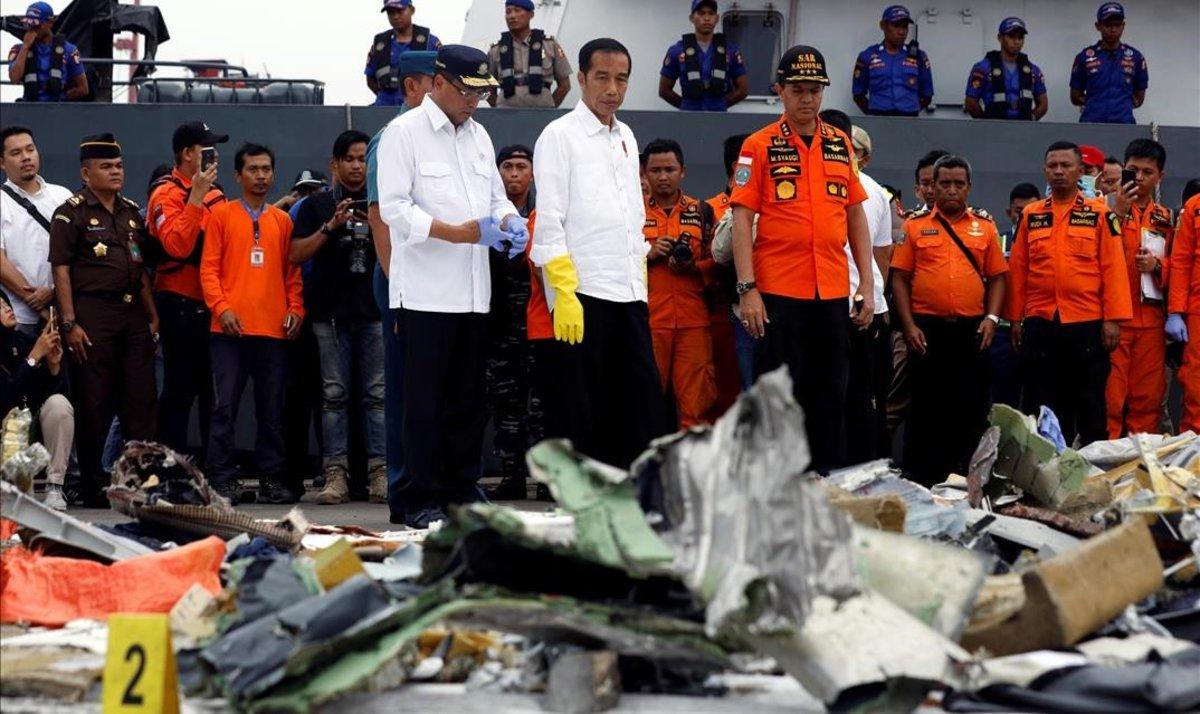 El presidente indonesio, Joko Widodo (centro), inspecciona algunos de los restos del avión de Lion Air siniestrado.