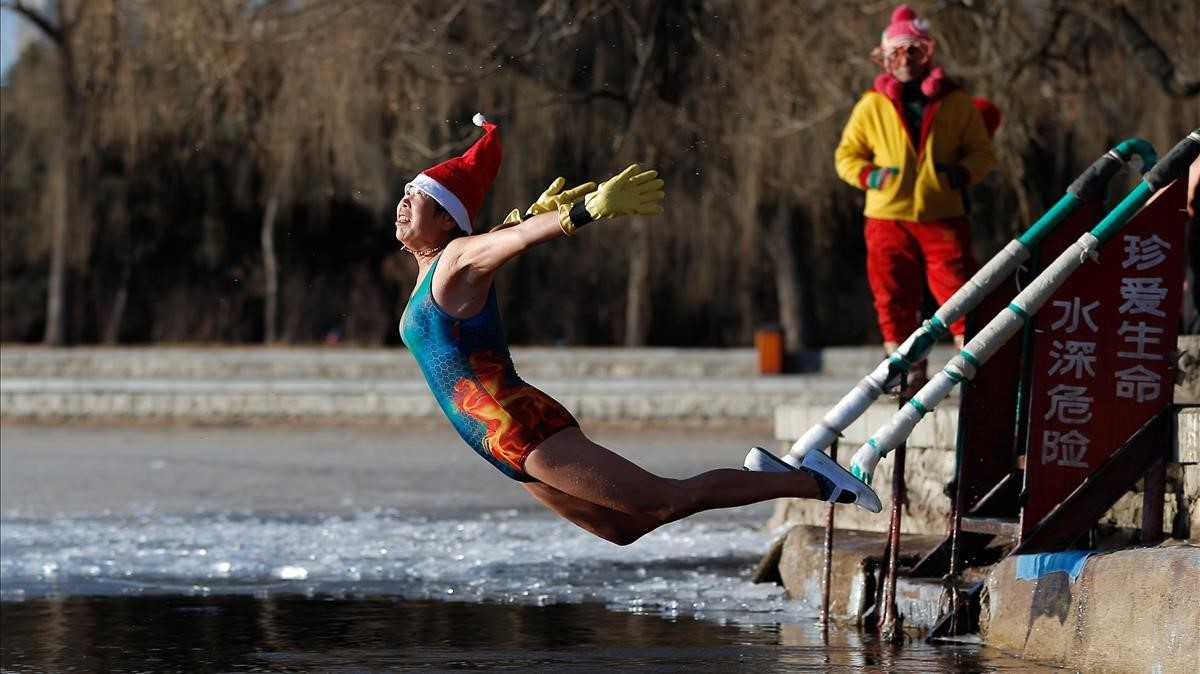 Una mujer con un sombrero de Papá Noel se zambulle en un lago parcialmente congelado en Shenyang, en la provincia de Liaoning, noreste de China.