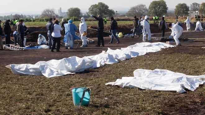 Suben a 107 los muertos por la explosión de una toma ilegal de gasolina en México. En la foto, expertos forenses registran la zona tras el accidente.