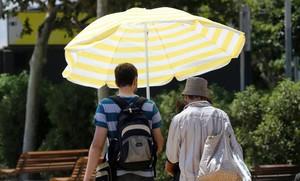 Turistas pasean con una sombrilla por Barcelona.