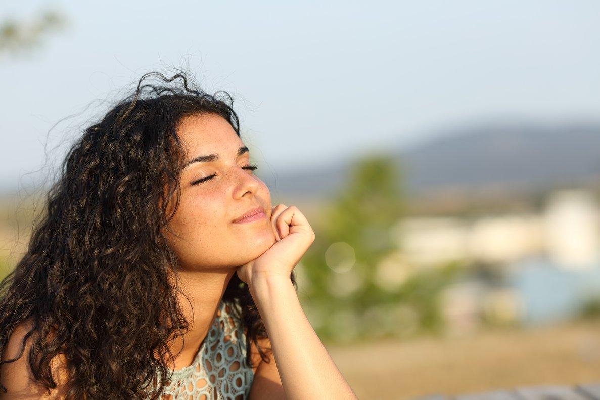 Una chica sonríe con los ojos cerrados.