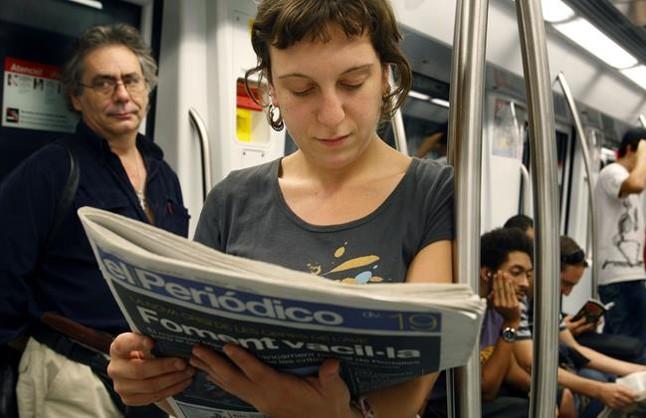 Una joven ojea un ejemplar de EL PERIÓDICO en el metro.