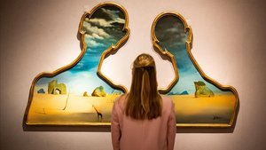 Una mujer, frente al cuadro de Dalí 'Couple aux têtes pleines de nuages' .