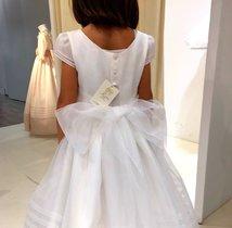 Una niña se prueba un vestido de comunión, en una tienda de Madrid.