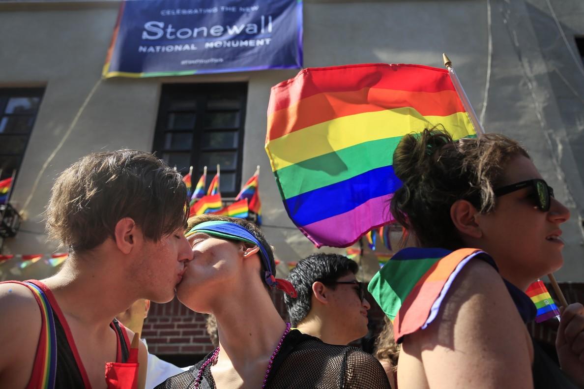 Una pareja de gais se besan frente al Stonewall, declarado monumento nacional, durante la Pride Parade de Nueva York.