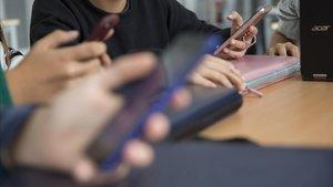 Unos estudiantes consultan sus teléfonos móviles en una clase.
