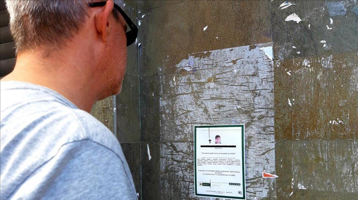 Un vecino de Getxo (Bizkaia) observa la esquela del niño de 13 años hallado muerto en el acantilado de La Galea.
