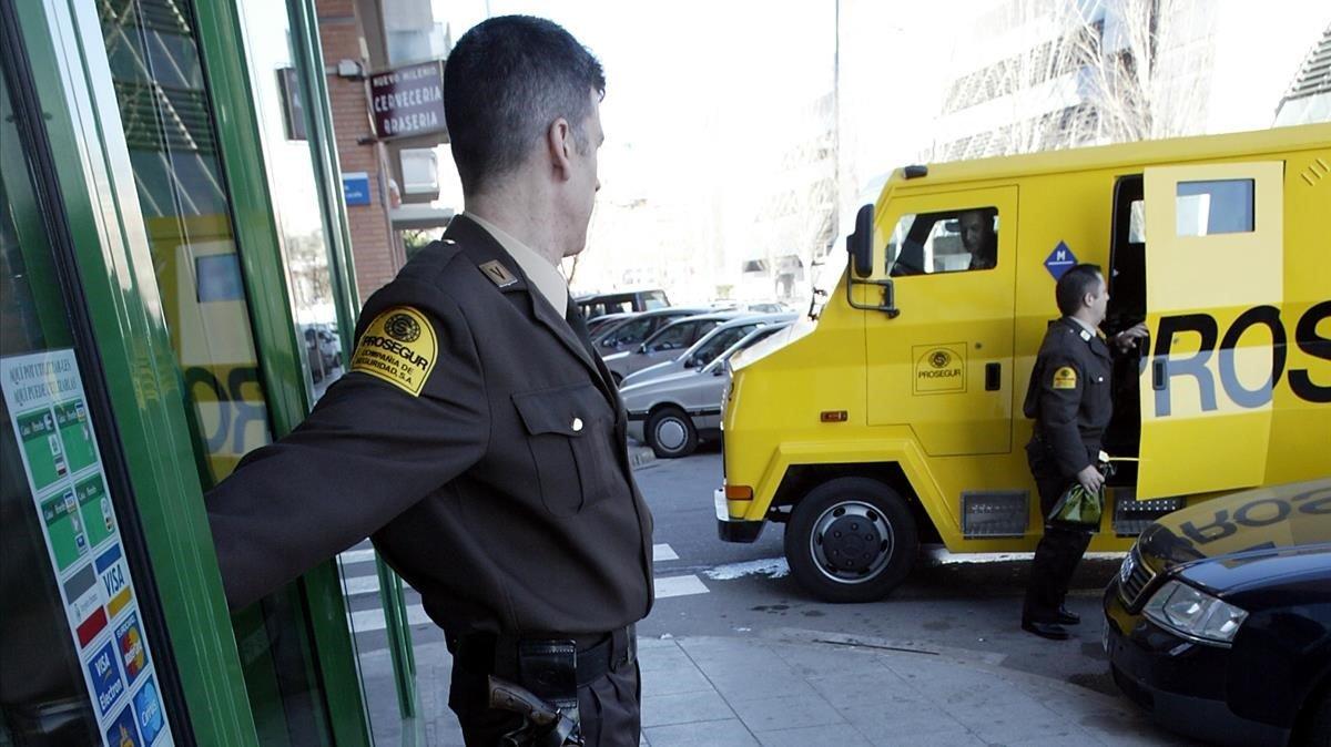 Dos vigilantes de seguridad de la empresa Prosegur, frente a un furgón blindado.
