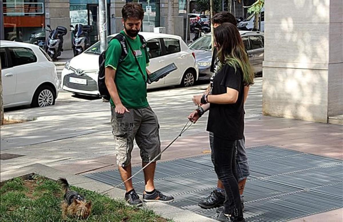 Uno de los informadores charla con el propietario de un perro en una zona verde del Eixample, este viernes.