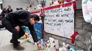 Un hombre coloca una flor en el memorial improvisado a las víctimas del atropello en Toronto.