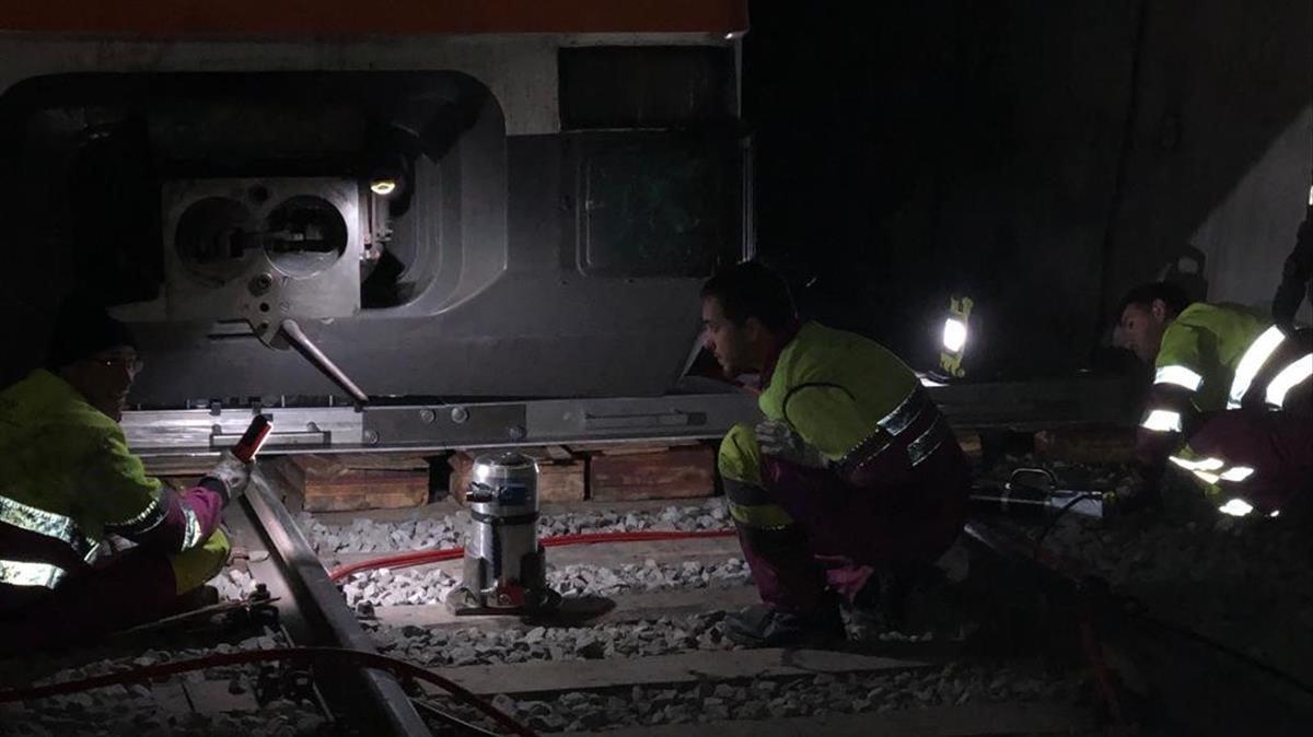 Tñécnicos de Renfe trabajan para encarrilar el tren y sacarlo del túnel, en la madrugada del miércoles.