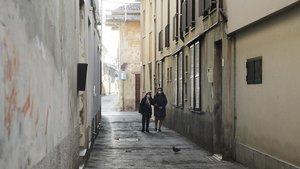 Vecinas de Cadogno, con máscaras, paseando por el pueblo semidesierto.