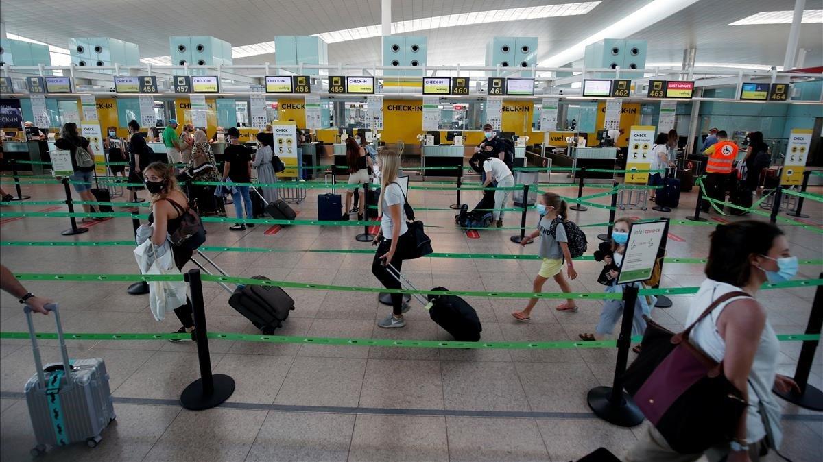 Colas para embarcar en el aeropuerto de El Prat este domingo.