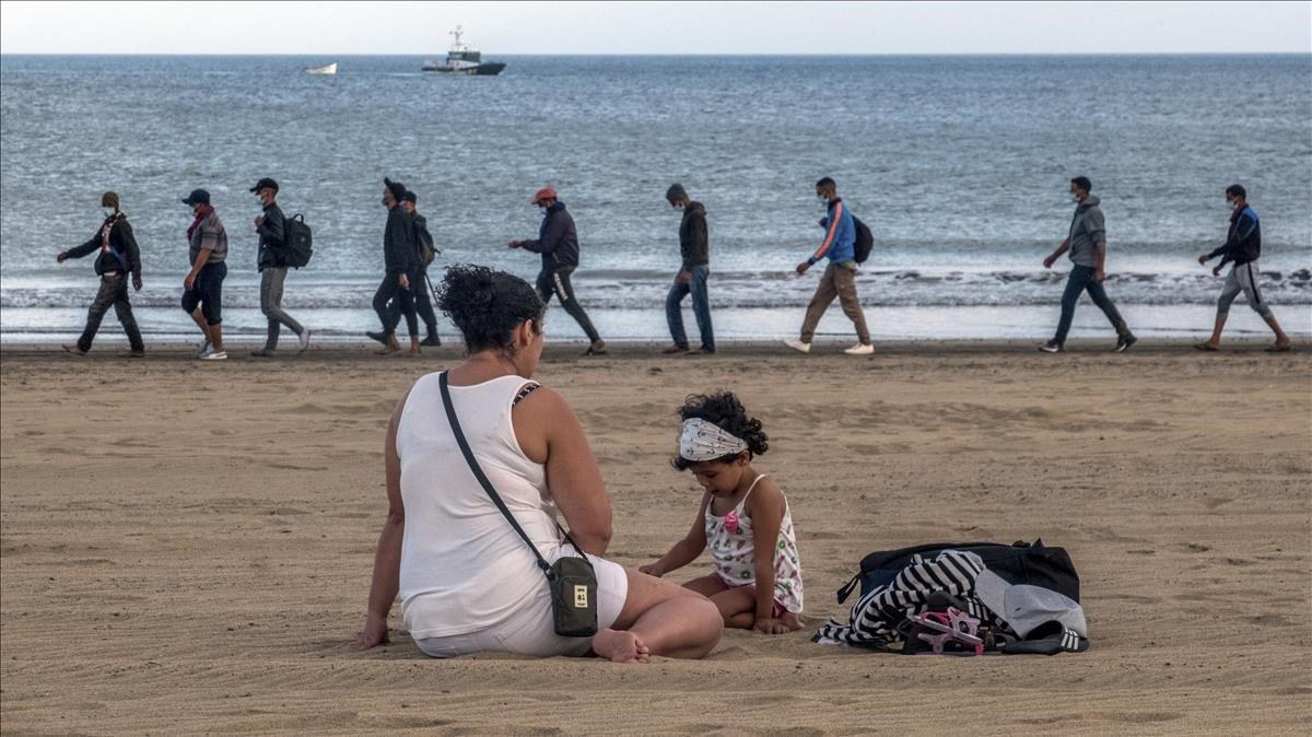 Policías españoles escoltan a un grupo de inmigrantes marroquís en una playa canaria.