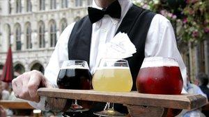 Un camararo sujeta tres vasos de cerveza con los colores de la bandera belga durante el festival de cerveza de Bruselas