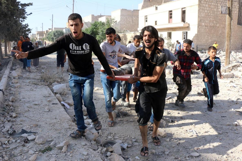 Varios habitantes trasladas a una víctima del bombardeo sobre la localidad de Manbij.