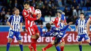 El delantero uruguayo del Alavés Diego Rolan remata ante el centrocampista del Girona Alex Granell