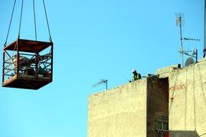 Imagen de un operario en lo alto del edificio de Badalona afectado con aluminosis en las tareas de derribo.