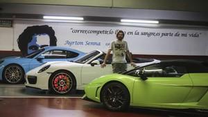 Xavi Matamoros, el encargado del Parking Villur,junto a dos Porsches yunLamborghini aparcados frente auna frasemíticade Ayrton Senna.