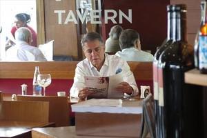 Joaquim María Puyal repasa la prensa mientras desayuna en una cafeteria junto a su despacho.