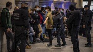 Agentes de los Mossos d'Esquadra cachean e identifican a varios jóvenes que participaron en las protestas de Barcelona el pasado fin de semana.