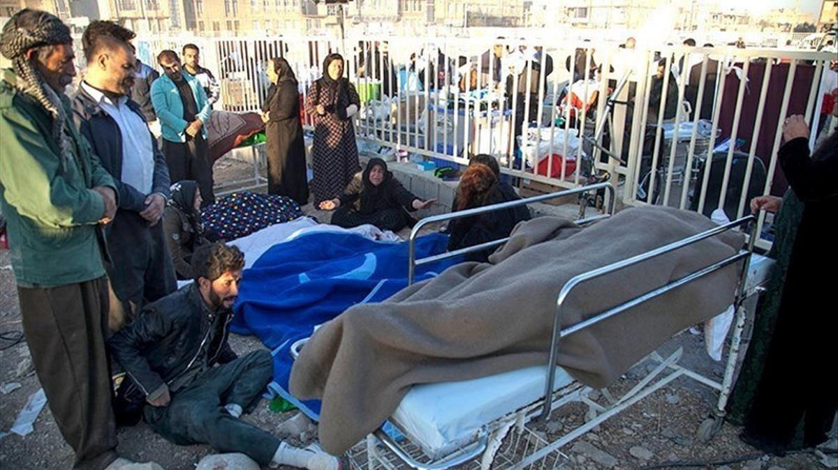 Las personas reaccionan al dolor junto a los cadáveres en el condado Sarpol-e Zahab en Kermanshah, Irán.
