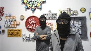 Los dos artistas que hay detrás de Me Lata posan encapuchados en Artevistas Gallery. Su exposición se puede visitar hasta el 6 de enero.