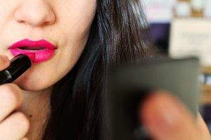 Una mujer se pinta los labios.