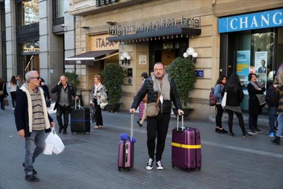 MENOS TURISTAS Unos huéspedes salen con sus maletas de un hotel.