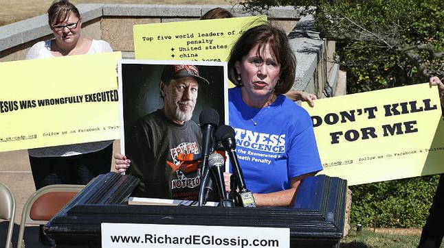 Nancy Vollertsen, con la foto de su hermano, Greg Wilhoit,quien pasó cinco años en el corredor de la muerte de Oklahoma antes de ser exonerado, por participar en una manifestación para detener la ejecución de Richard Glossip.