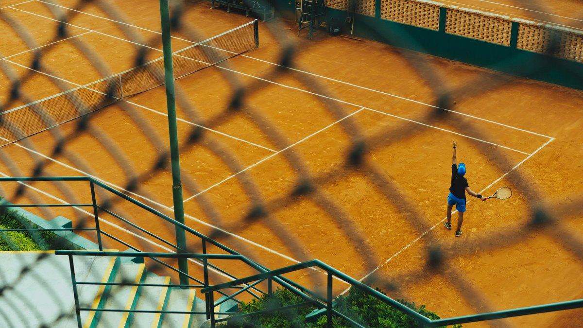 Hombre que juega al tenis en una cancha.