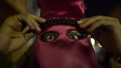 Un penitente se ajusta la vestimenta momentos antes de participar en la procesión de Calahorra.
