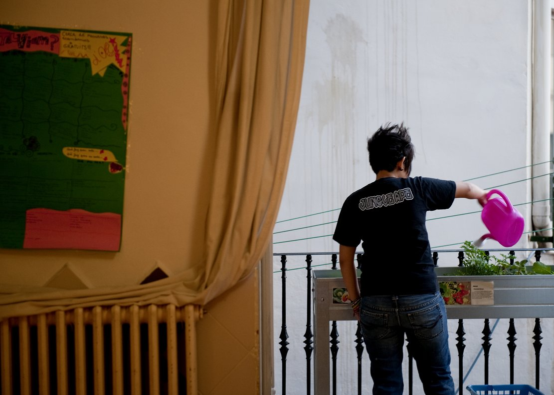 Una joven riega el huerto de su balcón, en Barcelona.