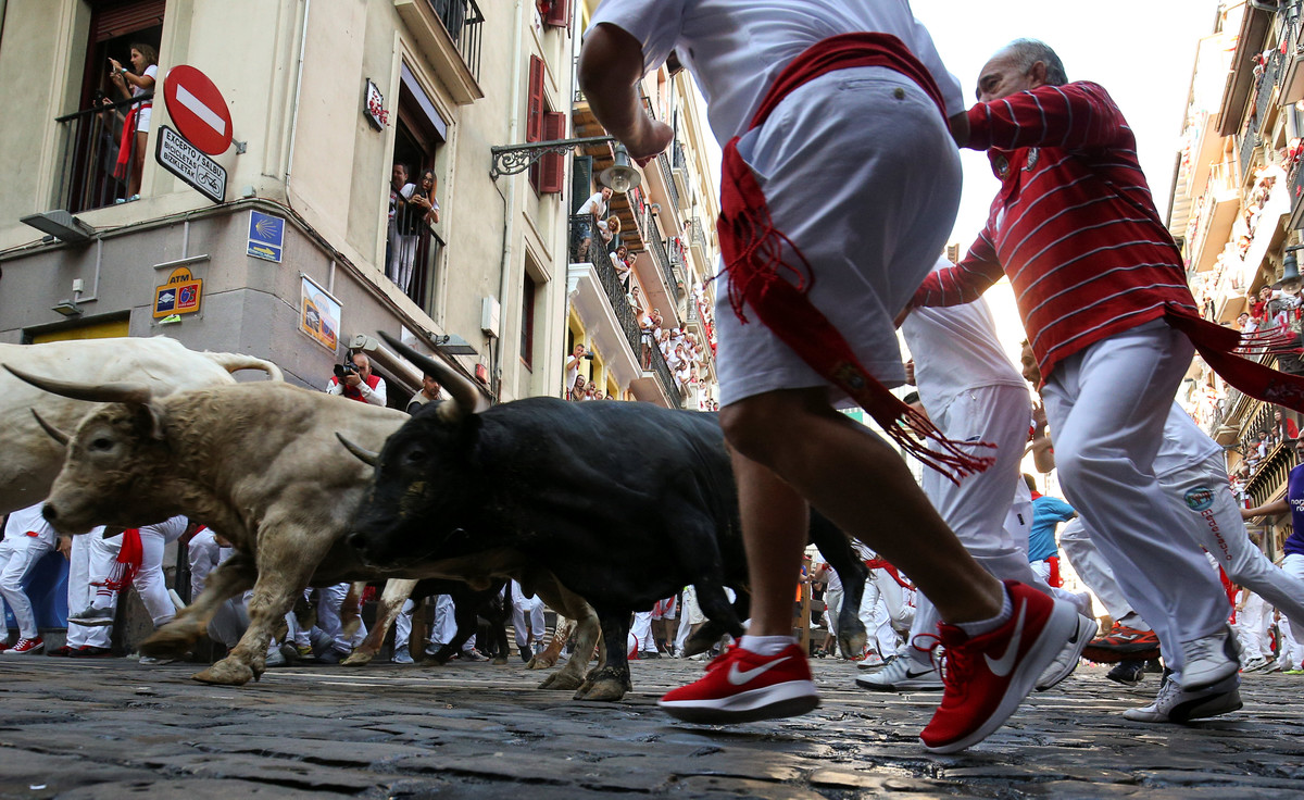 Revellers sprint in front of bulls during the fifth running of the bulls of the San Fermin festival in Pamplona, Spain, July 11, 2018. REUTERS/Susana Vera