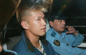 Satoshi Uematsu (izquierda), sentado en un vehículo policial.