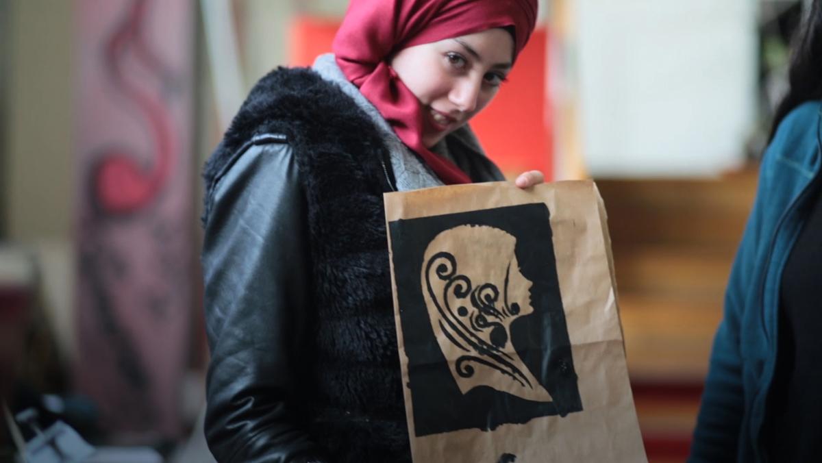 Mujeres jóvenes migrantes organizadasen un taller de serigrafía.