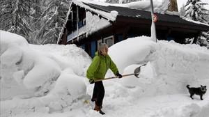 Una mujer aparta la nieve en Val DIsere, en los Alpes franceses.