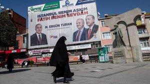 Una mujer camina frente a un cartel electoral que muestra al presidente turno, Recep Tayyip Erdogan, y al candidato de su partido, el AKP, para la alcaldía de Estambul. Binali Yildirim.