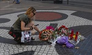 Una mujer deposita flores en La Rambla, en la víspera del primer aniversario del atentado del 17A.