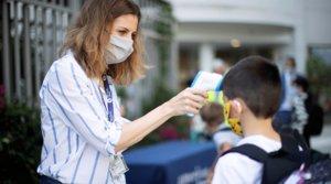 Una trabajadora toma la temperatura a un niño a la entrada del colegio privado internacional American School of Barcelona, en Esplugues de Llobregat (Barcelona), el lunes 1 de septiembre.