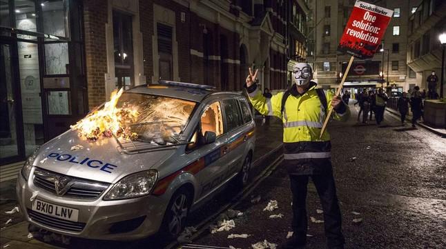 Uno de los manifestantes de Anonymous delante del vehículo de policía quemado durante la Marcha de las mil máscaras.