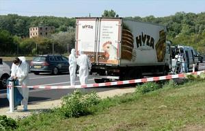 Unos forenses inspeccionan el camión donde fueron hallados los cadáveres.