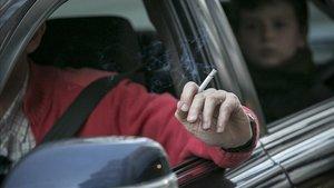 Un conductor fumando mientras conduce, con un menor detrás.
