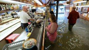 Clientes de un bar, con el agua hasta por encima de las rodillas, este domingo.