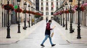 Una persona con mascarilla cruza la calle Larios de Málaga durante el confinamiento decretado por la pandemia de coronavirus