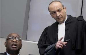 El expresidente de Costa de Marfil, Laurent Gbagbo, habla con su abogado en el Tribunal de La Haya.
